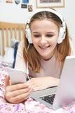 Adolescente que escucha la música mientras que usa el teléfono móvil Fotos de archivo libres de regalías