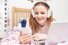 Adolescente que escucha la música mientras que usa el teléfono móvil Foto de archivo