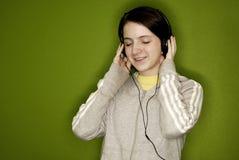 Adolescente que escucha los ojos de los auriculares de la música cerrados Imagen de archivo libre de regalías