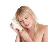 Adolescente que escucha un seashell Fotografía de archivo libre de regalías