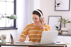 Adolescente que escuta a música ao fazer trabalhos de casa imagens de stock