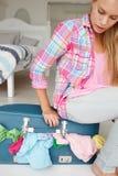 Adolescente que esforça-se para fechar a mala de viagem Imagem de Stock
