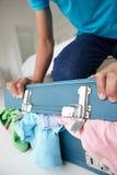 Adolescente que esforça-se para fechar a mala de viagem cheia Fotografia de Stock Royalty Free