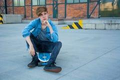 Adolescente que espera, sittin en patín Imagen de archivo