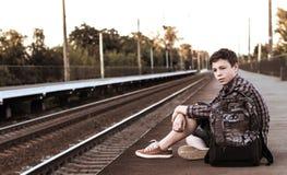 Adolescente que espera un tren en la estación Fotos de archivo