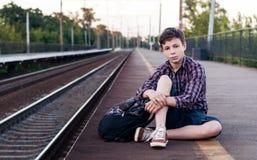 Adolescente que espera un tren en la estación Foto de archivo libre de regalías