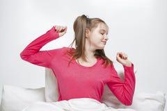 Adolescente que estira en cama Imagen de archivo libre de regalías