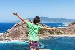 Adolescente que estira su frente de mar de los brazos en Cerdeña Fotografía de archivo
