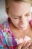 Adolescente que estornuda en tejido Fotografía de archivo