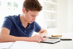 Adolescente que estuda usando a tabuleta de Digitas em casa Imagem de Stock