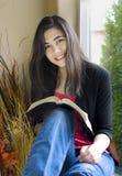 Adolescente que estudia al lado de ventana asoleada Fotos de archivo