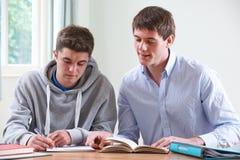 Adolescente que estudia con el profesor particular casero Fotografía de archivo