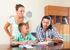 Adolescente que estudia con los padres Fotografía de archivo