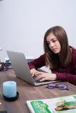 Adolescente que estudia con un ordenador Fotografía de archivo