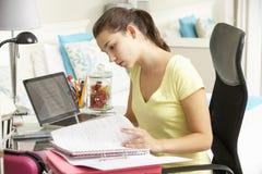 Adolescente que estudia en el escritorio en dormitorio Fotos de archivo libres de regalías