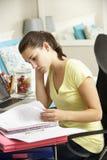 Adolescente que estudia en el escritorio en dormitorio Imagen de archivo libre de regalías