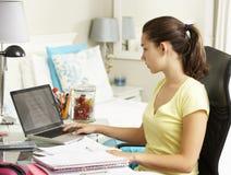 Adolescente que estudia en el escritorio en dormitorio Imagenes de archivo