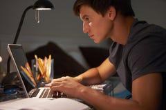 Adolescente que estudia en el escritorio en dormitorio por la tarde en el ordenador portátil Imagenes de archivo
