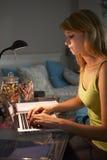 Adolescente que estudia en el escritorio en dormitorio por la tarde en el ordenador portátil Fotos de archivo libres de regalías
