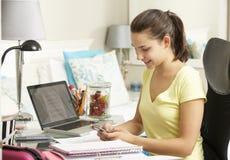 Adolescente que estudia en el escritorio en dormitorio usando el teléfono móvil Foto de archivo libre de regalías