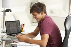 Adolescente que estudia en el escritorio en dormitorio usando el teléfono móvil Foto de archivo