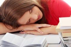 Adolescente que estudia en el escritorio que es cansado Imagen de archivo libre de regalías