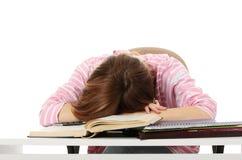 Adolescente que estudia en el escritorio que está cansado Foto de archivo