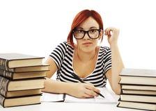 Adolescente que estudia en el escritorio que está cansado Foto de archivo libre de regalías