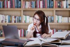 Adolescente que estudia en la biblioteca Fotos de archivo