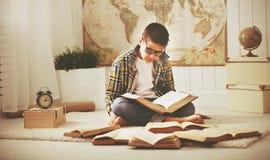 Adolescente que estudia, libros del muchacho de lectura, preparándose para los exámenes en el hom Imagenes de archivo