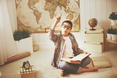Adolescente que estudia, libros del muchacho de lectura, preparándose para los exámenes en el hom Fotografía de archivo