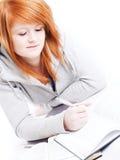 Adolescente que estudia y que hace algunas notas Foto de archivo