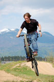 Adolescente que faz truques na bicicleta Fotos de Stock Royalty Free