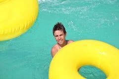 Adolescente que flota en círculo amarillo Foto de archivo