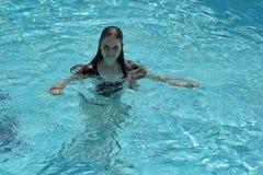 Adolescente que flota en la piscina Imagen de archivo libre de regalías
