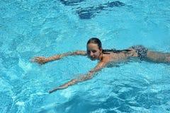 Adolescente que flota en la piscina Fotografía de archivo