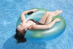 Adolescente que flota en tubo en piscina Fotos de archivo libres de regalías