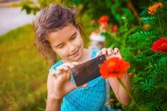 Adolescente que fotografía el teléfono de la flor en un verde Fotografía de archivo