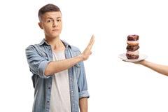 Adolescente que gesticula la parada con su mano a una pila de anillos de espuma encendido fotos de archivo libres de regalías