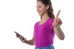 Adolescente que gesticula mientras que usa el teléfono móvil Fotografía de archivo