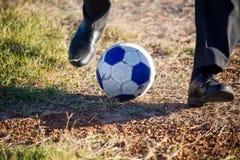 Adolescente que golpea el balón de fútbol con el pie Fotos de archivo