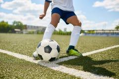 Adolescente que golpea la bola con el pie en campo de fútbol Fotografía de archivo