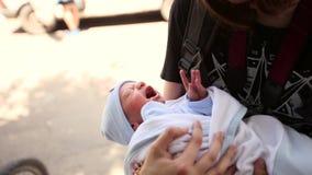 Adolescente que guarda um bebê recém-nascido em seus braços Contorcer-se o cuidados video estoque