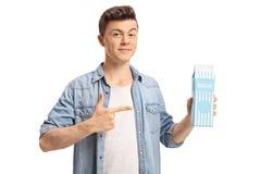 Adolescente que guarda uma caixa e apontar do leite imagens de stock royalty free