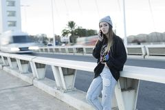 Adolescente que habla en el teléfono móvil al lado de un camino Fotografía de archivo