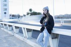 Adolescente que habla en el teléfono móvil al lado de un camino Fotos de archivo