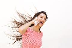 Adolescente que habla en el teléfono móvil con el pelo que sopla del viento Imagen de archivo
