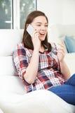 Adolescente que habla en el teléfono móvil en casa Imágenes de archivo libres de regalías