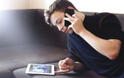Adolescente que habla en el teléfono que miente en el sofá Fotos de archivo