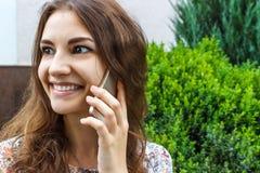 Adolescente que habla en el teléfono en parque en verano Fotografía de archivo libre de regalías